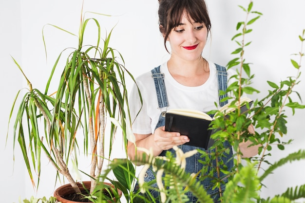 Young female florist with diary looking at plants