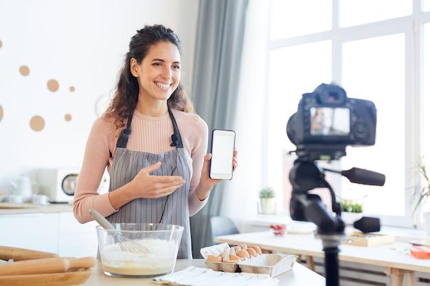 カメラで新しい携帯電話アプリケーションをデモンストレーションする若い女性の食品ブロガー
