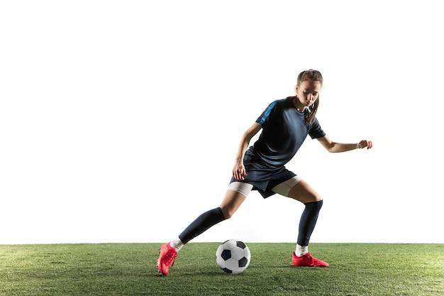 スポーツウェアとブーツで長い髪の若い女性のサッカー選手またはサッカー選手は、白い背景で隔離のジャンプでゴールのためにボールを蹴ります。健康的なライフスタイル、プロスポーツ、趣味の概念。