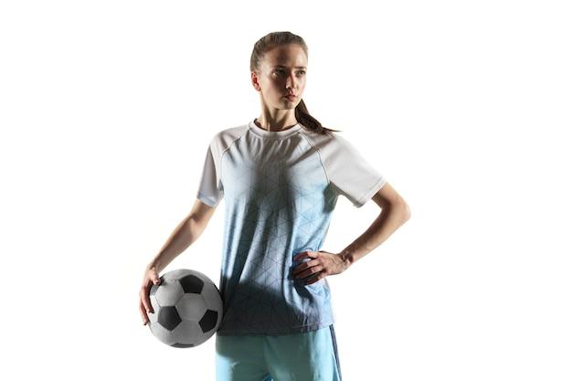スポーツウェアとブーツで長い髪の若い女性のサッカー選手またはサッカー選手は、白い背景で隔離のボールで立っています。健康的なライフスタイル、プロスポーツ、趣味の概念。