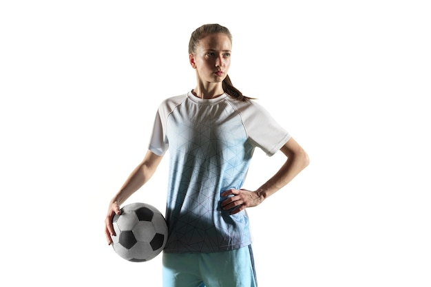Young female football or soccer player with long hair in sportwear and boots standing with the ball isolated on white background. concept of healthy lifestyle, professional sport, hobby.