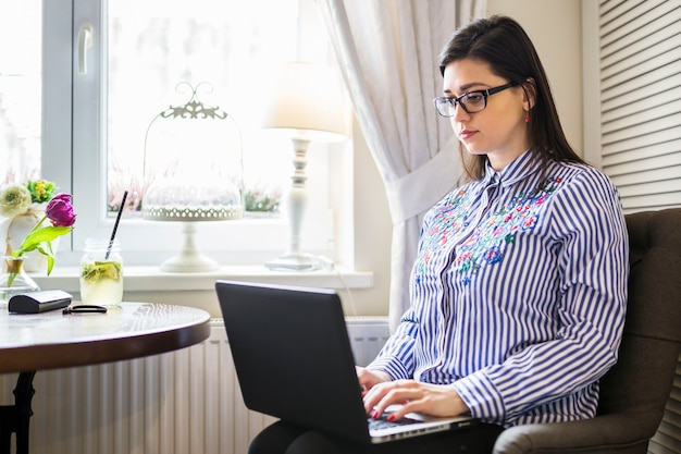 Young female freelance using laptop at home