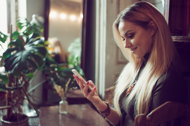 Young female freelancer chatting on mobile phone while sitting on the couch in vintage cafe