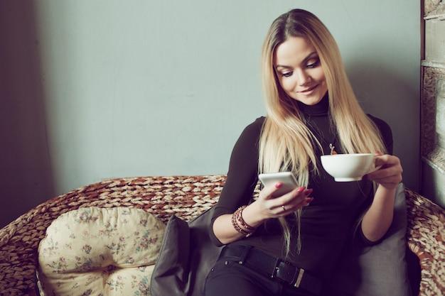 Молодая женщина фрилансер в чате на мобильном телефоне, сидя на диване в винтажном кафе