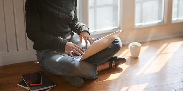 Молодая женщина-фрилансер печатает на ноутбуке, сидя рядом с окнами