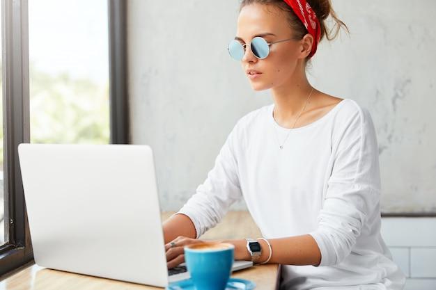 젊은 여성 프리랜서는 카페, 키보드 정보, 음료 커피의 랩톱 컴퓨터에서 원격으로 작동합니다. 레스토랑에서 무선 인터넷에 연결된 소셜 네트워크에서 친구와 여자 채팅