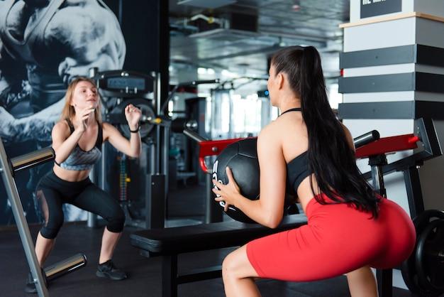 Молодые подруги, одетые в спортивную одежду, делают глубокие приседания