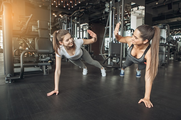 Young female friends exercise in the gym workout