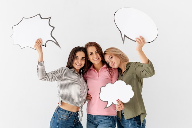 Young female friends holding chat bubble