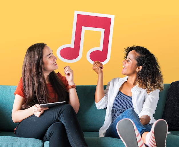 Young female friends holding a musical note icon