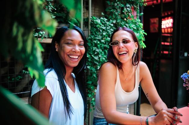 Молодые подруги улыбаются и наслаждаются временем вместе, сидя в саду ресторана или кафе. понятие дружбы.