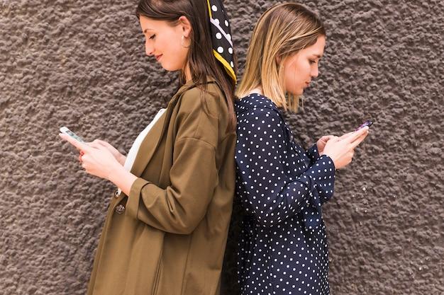 Молодые женщины-друзья, стоящие спиной к спине с помощью мобильного телефона