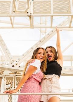 Young female friends standing under the ferris wheel enjoying