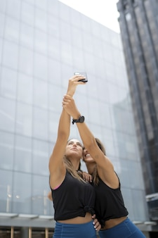 Young female friends walking near buildings and taking selfies at daytime