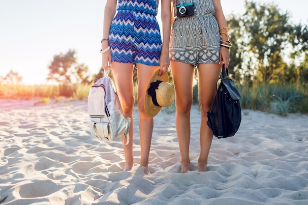 Young female friends  walking together on a beach at sunset