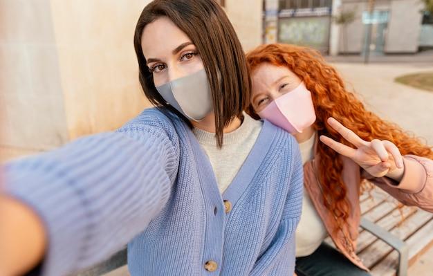 セルフィーを取る屋外でフェイスマスクを持つ若い女性の友人