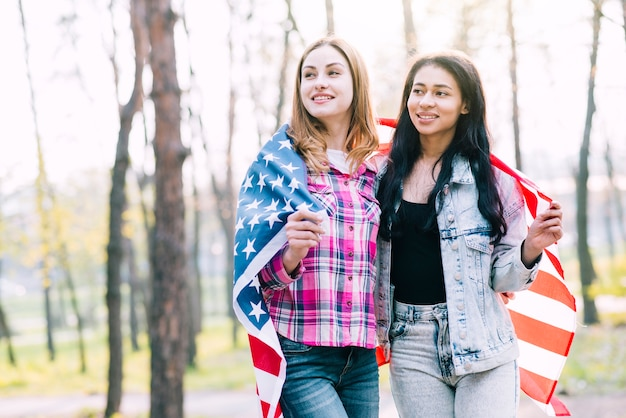 Young female friends wrapping in american flag