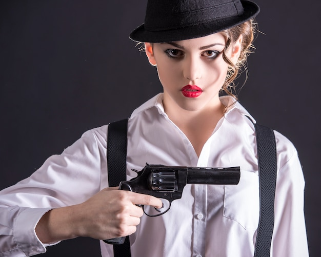 Young female gangster holding the gun.
