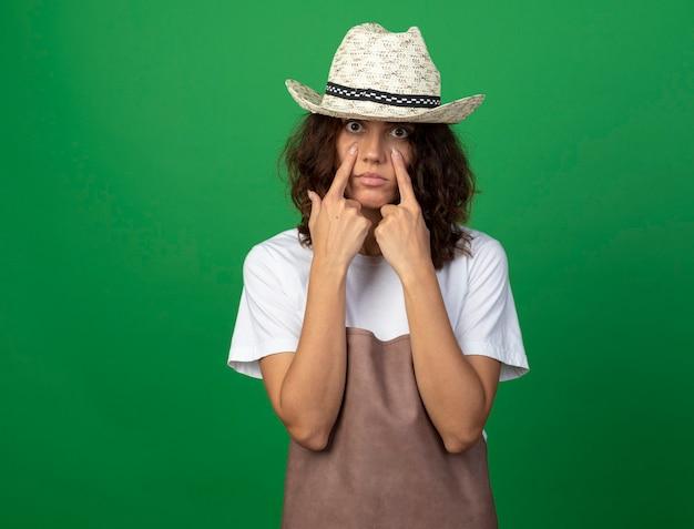 눈 뚜껑을 아래로 당기는 원예 모자를 쓰고 제복을 입은 젊은 여성 정원사