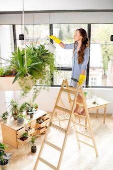오렌지 온실의 사다리에 물을 깡통으로 서 있는 식물을 돌보는 젊은 여성 정원사
