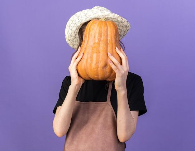 호박으로 얼굴을 덮은 원예 모자를 쓴 젊은 여성 정원사