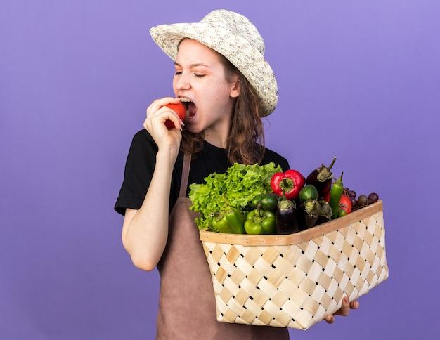 野菜のバスケットとトマトのかみ傷を保持しているガーデニング帽子をかぶっている若い女性の庭師