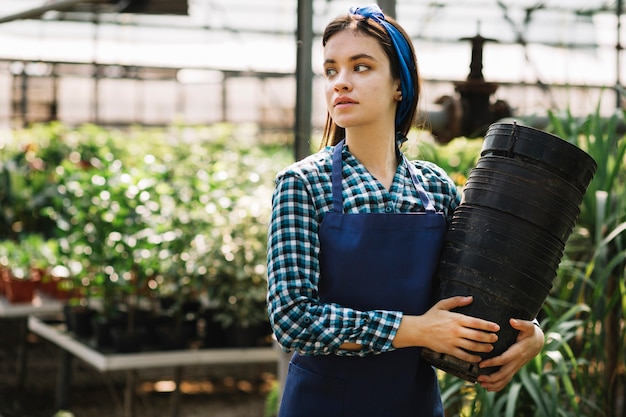 Young female gardener with empty flower pots in greenhouse