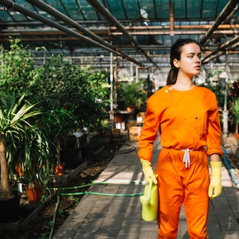 Young female gardener with watering can standing in greenhouse