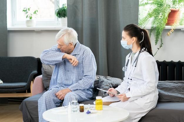 彼女の前のソファに座って咳やくしゃみをする病気の年配の男性を見ているタッチパッドを持つ若い女性の一般開業医