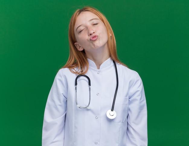 Giovane dottoressa allo zenzero che indossa una tunica medica e uno stetoscopio che fa un gesto di bacio con gli occhi chiusi