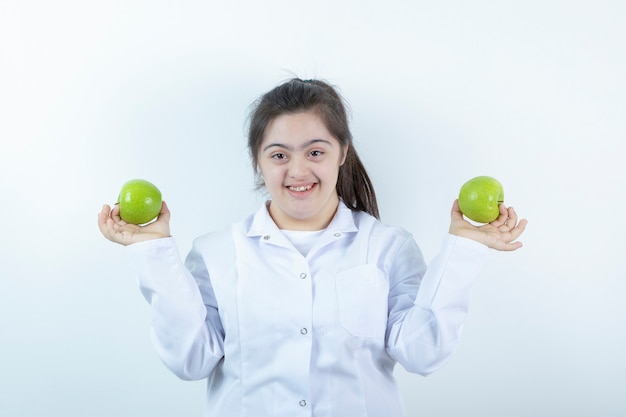 Young female girl in doctor's uniform holding green apple fruits in hands .