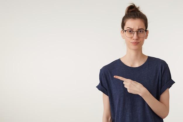 Giovane donna in bicchieri in t-shirt che punta da parte con irritazione, in piedi sul muro bianco