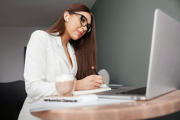 Young female in glasses using laptop, communicates on internet with customer in home, coffee mug on table.cozy office workplace, remote work, elearning concept