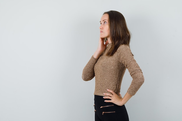 Young female in golden blouse looking aside and looking pensive . space for text