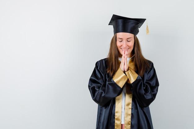 Giovane donna laureata in abito accademico premendo le mani insieme per pregare e guardando speranzoso, vista frontale.