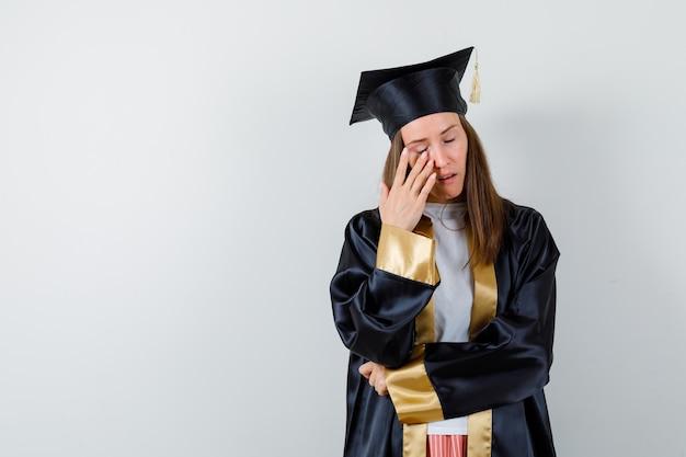 Молодая женщина-выпускница в академической одежде закрывая глаз и глядя надежды, вид спереди.