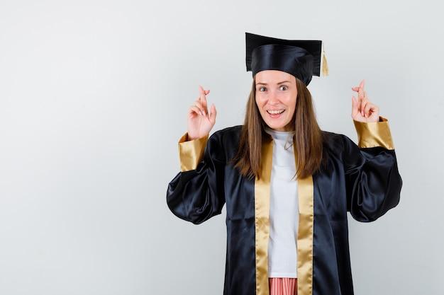 고립 된 교차 손가락을 보여주는 학술 드레스에 젊은 여성 대학원