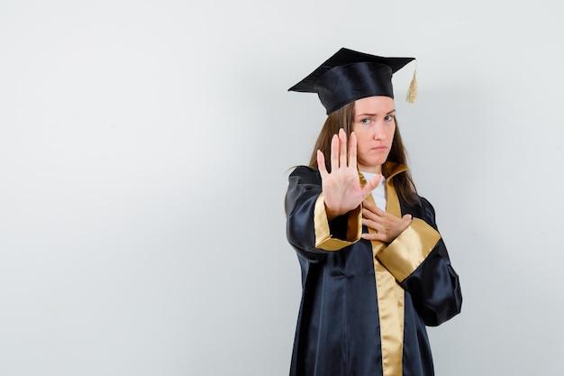 학술 드레스에 중지 제스처를 보여주는 젊은 여성 대학원 심각한, 전면보기를 찾고.