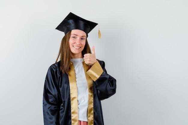 Молодая женщина-выпускница показывает большой палец вверх в академической одежде и выглядит счастливой. передний план.