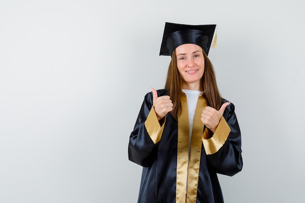 Young female graduate showing thumps up in academic dress and looking blissful , front view.