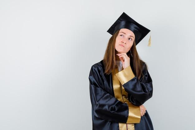 학술 드레스에 생각 포즈와 사려 깊은 찾고 젊은 여성 대학원 서. 전면보기.