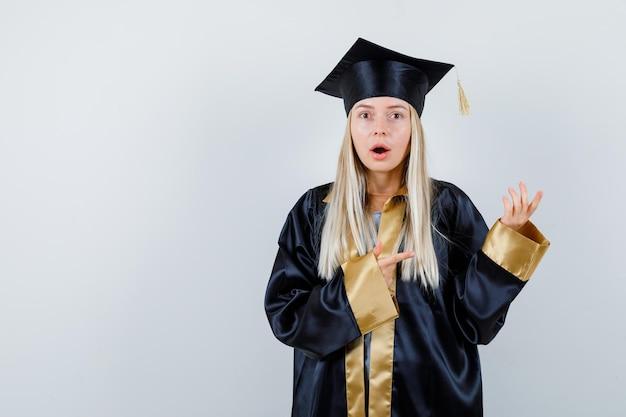 Giovane donna in uniforme laureata che punta da parte e sembra sorpresa