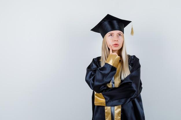 Giovane donna in uniforme da laureato in piedi in posa di pensiero e sembra esitante