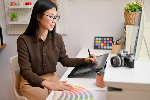 Young female graphic designer working on computer and drawing tablet on comfortable office room