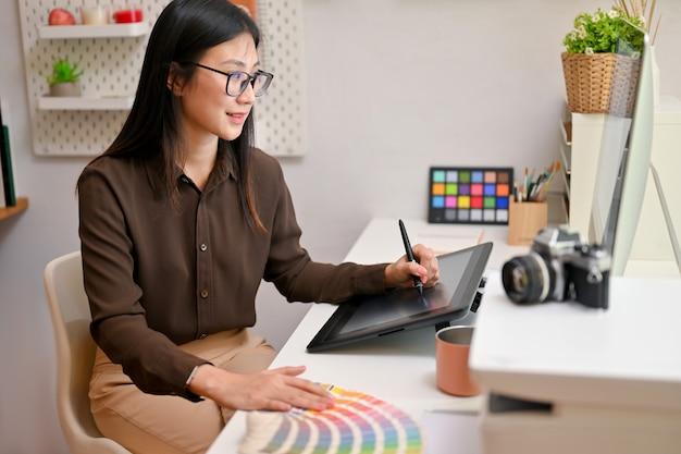 Молодой женский графический дизайнер работает на компьютере и рисовании на планшете в удобной офисной комнате