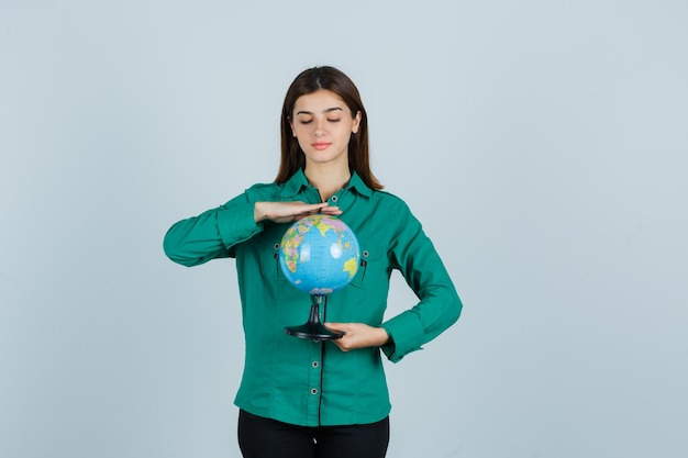 Young female in green shirt looking at earth globe and looking careful , front view.