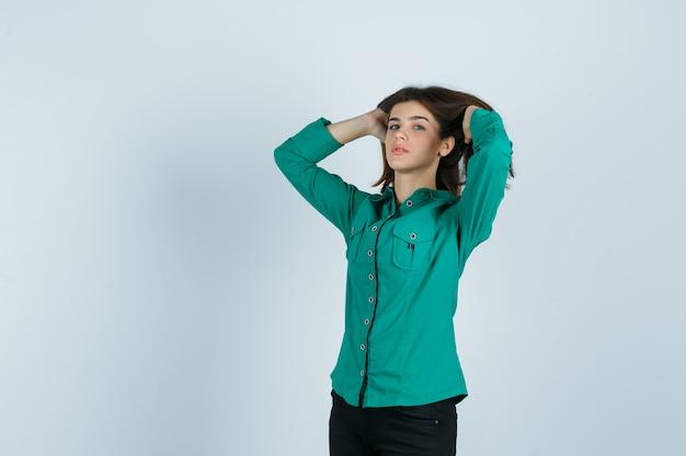 Giovane donna in camicia verde, pantaloni in posa con le mani tra i capelli castani e dall'aspetto seducente, vista frontale.