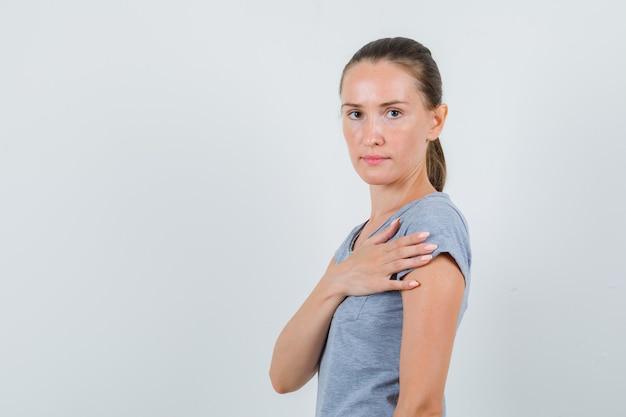 Giovane femmina in maglietta grigia che tiene la mano vicino al cuore e che sembra serio, vista frontale.