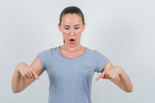 Giovane donna in maglietta grigia rivolta verso il basso e guardando sorpreso, vista frontale.