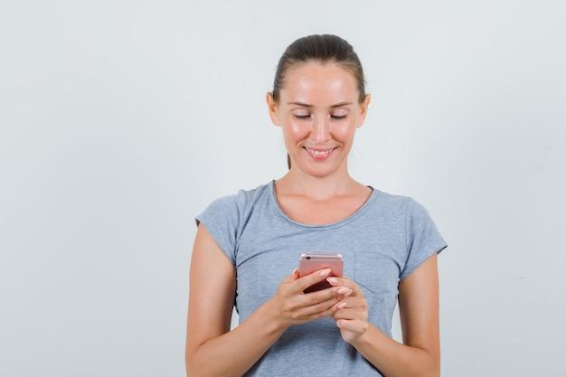 Giovane donna in maglietta grigia utilizzando il telefono cellulare e guardando allegro, vista frontale.